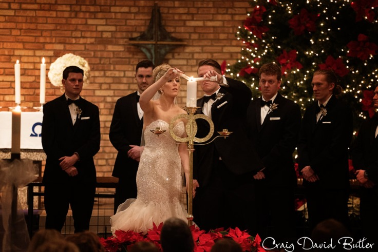 bride and groom light their unity candle at the wedding ceremony