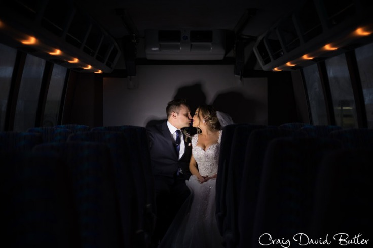 Bride and groom lowlight photo on the bus outside the ceremony venue.