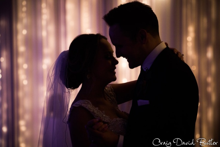Using the lighted wall behind the bride and groom for a silhouette photo.