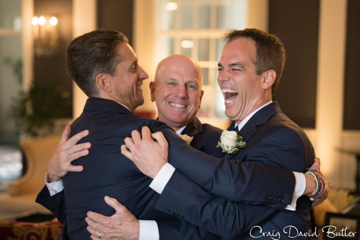 Groom having fun with dad and groomsmen