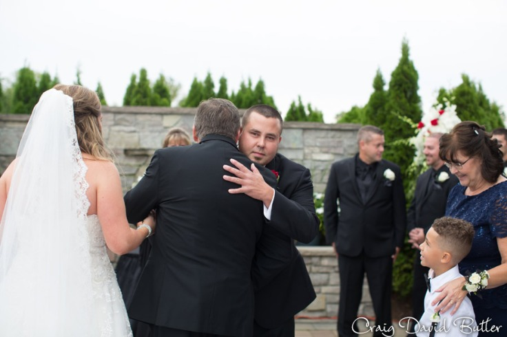 Father of the Bride hands of bride to Groom at wedding in the Diamond Center in Novi MI