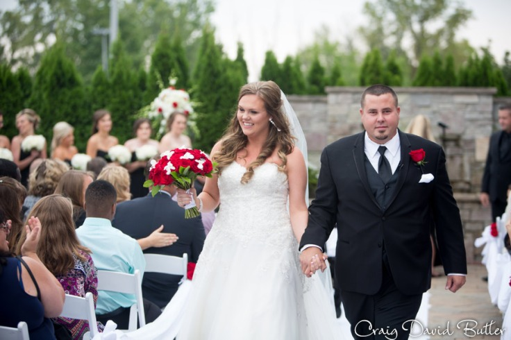 Lacey & George exit the wedding ceremony at the suburban showplace diamond center in NOvi MI