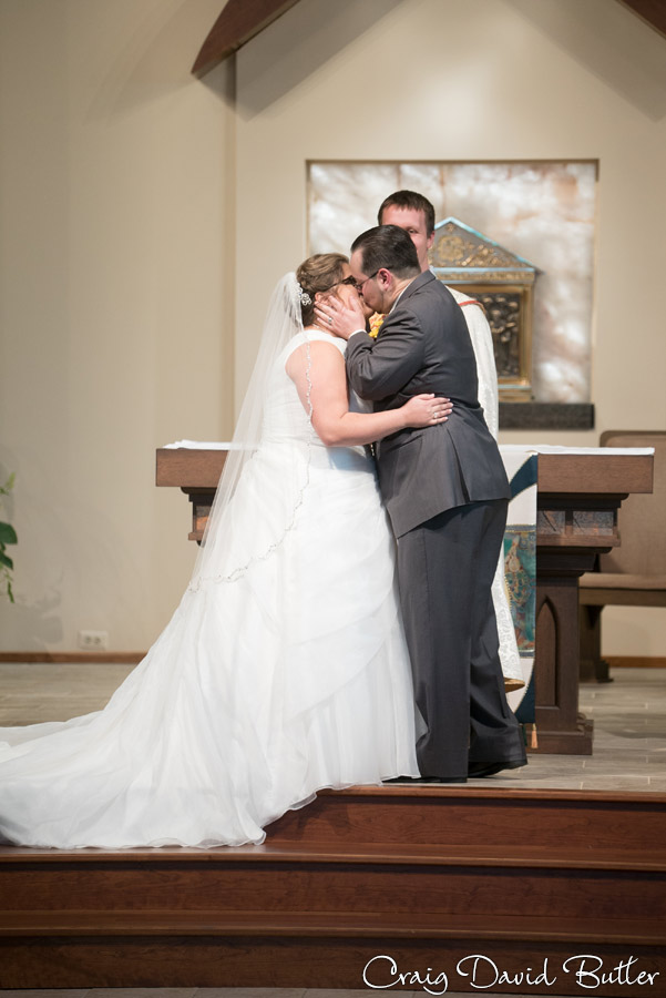 Bride and Groom's first kiss during the wedding ceremony at St. Patrick Church in Brighton MI
