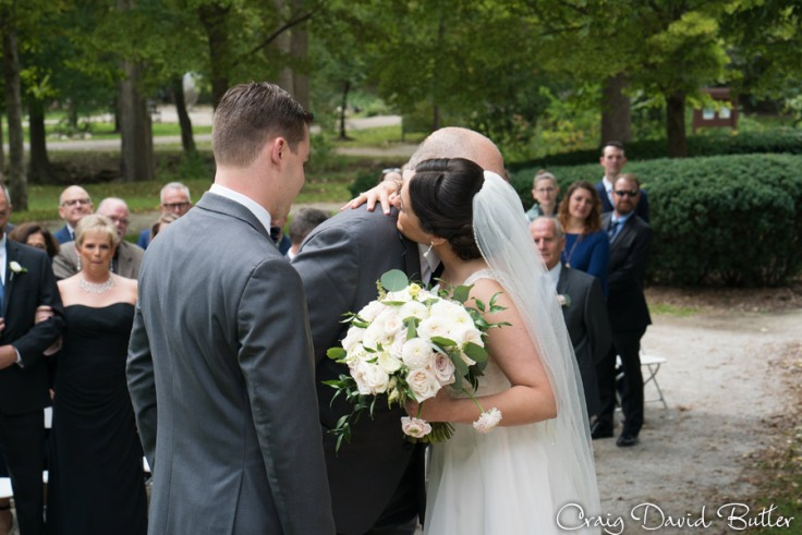 dad gives bride away during the wedding ceremony at Mill Race Village in Northville MI by Craig David Butler