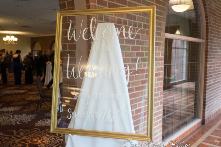 Framed glass wedding welcome sign at the wedding reception in the Grand Ballroom at the Inn at St. John's in Plymouth MI by Craig David Butler